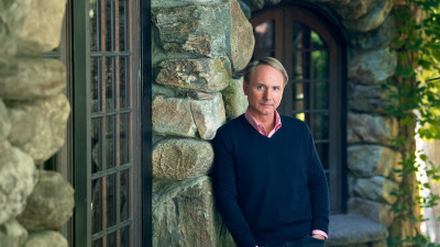 Dan Brown leaning against a wall in his MasterClass