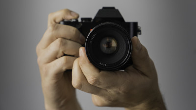 Man holding camera with gray background