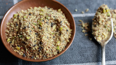 Dukkah spice in bowl and spoon on fabric