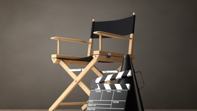 Black director's chair with movie clapper and megaphone