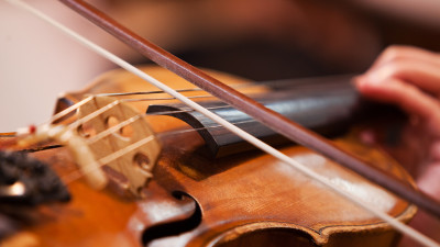Wooden violin with bow playing on strings