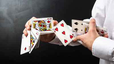 Desk of cards in hands with black background