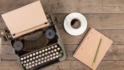 Typewriter with notebook and coffee on wood