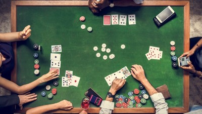 birds eye view of poker table with people playing cards