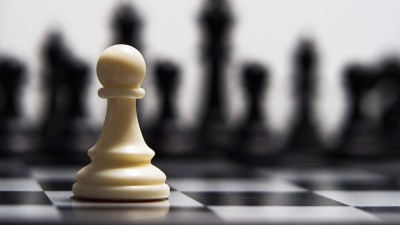 White chess piece with black pieces in background