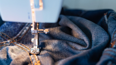 Pair of jeans being sewed by a sewing machine