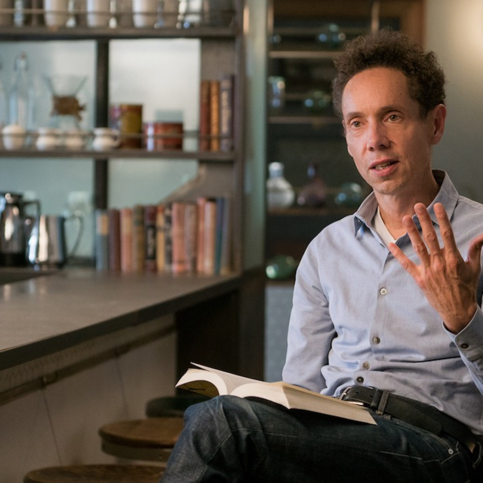 Malcolm Gladwell sitting with book explaining something