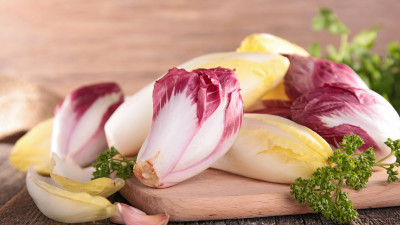 Raw yellow and purple chicories with parsley on wood