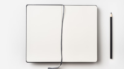 Black notebook with string and black pencil