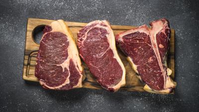 Three marbled steaks on wood board on black background
