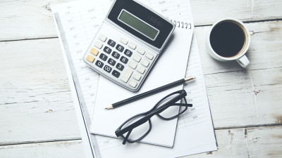Calculator with coffee, paper, glasses and pencil