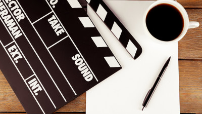 Movie clapperboard on piece of paper with coffee