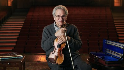 Itzhak Perlman sitting on stage with violin and case