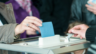 a person putting their ballot in the voting box