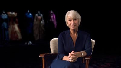 Helen Mirren sitting in chair in front of costumes