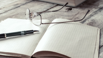 notebook with pen and glasses on wood table