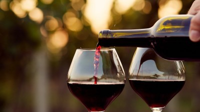 Red wine being poured into glass with bokeh background