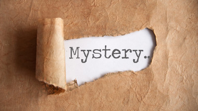 The word mystery being revealed by torn paper
