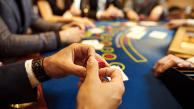 Person holding poker chips at poker table