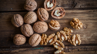 Shelled and unshelled walnuts on wood
