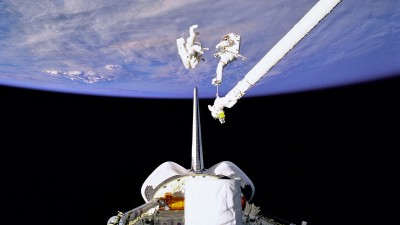 Canada Arm in space with astronauts near planet earth