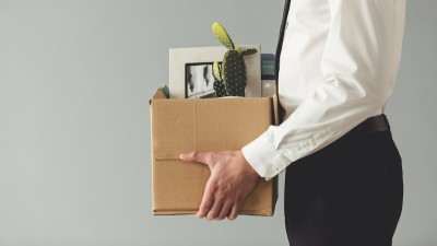 Person holding box with stuff in business clothes