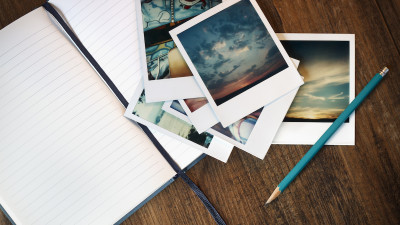 polaroid photos with notebook and pencil on wood