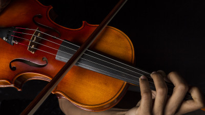 Person playing a violin with black background