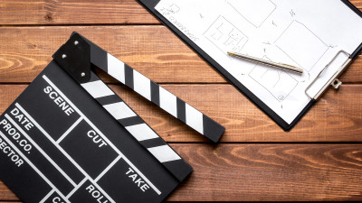 Movie clapperboard with clipboard on wood table