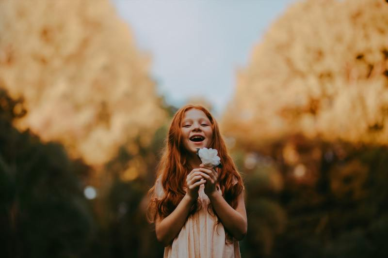 portrait photo of child with flower