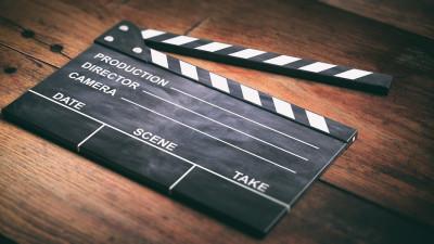 Movie clapperboard on dark wood