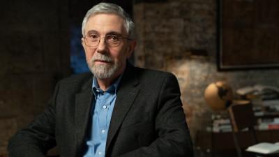 Paul Krugman sitting in chair in office