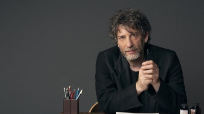 Neil Gaiman sitting at desk with writing materials