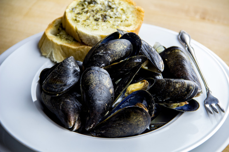 steamed mussels in a bowl with bread