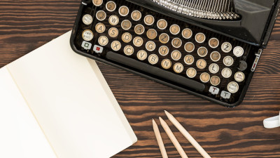 Vintage typewriter with notebook and pencils on wood