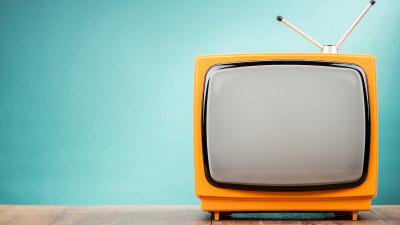 Retro old orange TV receiver on table front gradient aquamarine wall background.