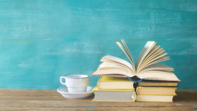 Stack of books with coffee cup on blue background