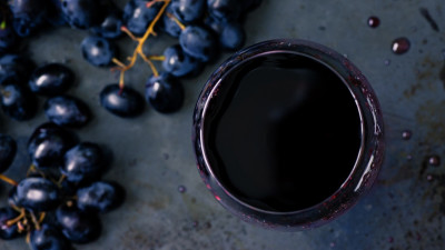 Red wine in glass with grapes on gray table