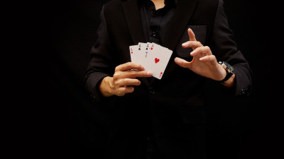 Man in black suit holding playing cards