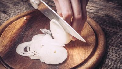 Person chopping onion on cutting board