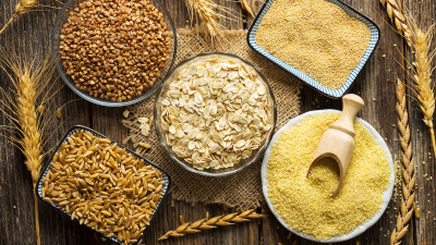 Various types of grains on wooden background with wheat