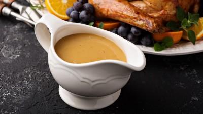 Gravy in gravy boat with turkey in background