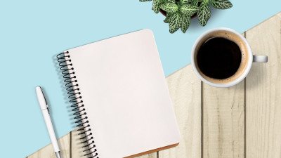Notebook with coffee and plant on blue and wood background