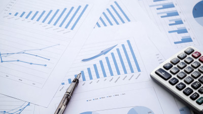 Blue charts on papers with pen and calculator