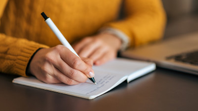 Person writing in notebook with yellow sweater