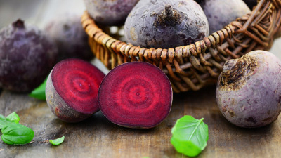 Cut raw beet with whole beets in basket