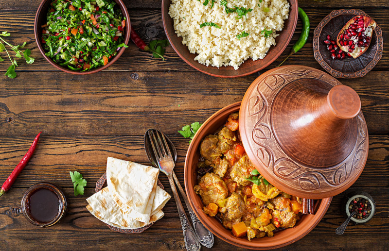 Tagine with food and ingredients on wood table