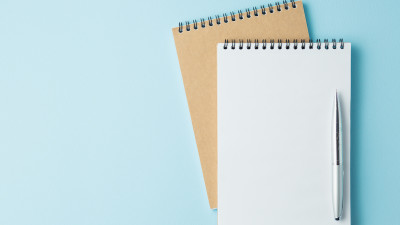 White and tan notebook with pen on blue background