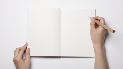 Woman writing in blank notebook with pencil