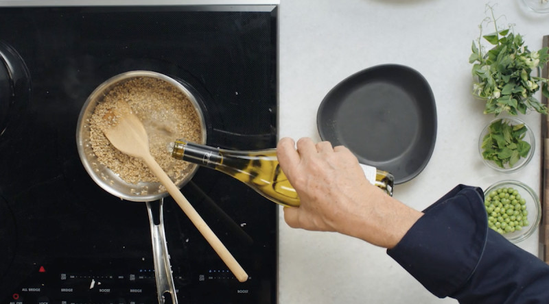 Wolfgang Puck pouring white wine into oats on stove